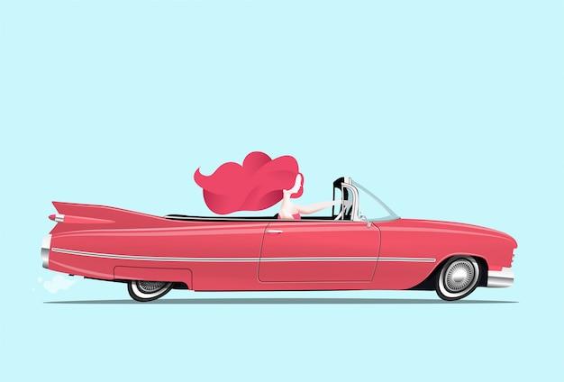Une rousse conduit une voiture cabriolet rouge classique