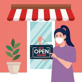 Rouvrir après la quarantaine, femme avec étiquette de réouverture du magasin, nous sommes à nouveau ouverts, magasin boutique façade