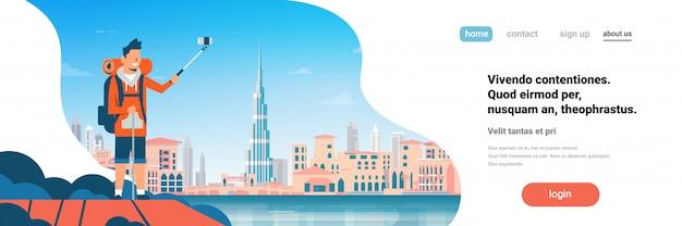 Sac à dos touristique homme prenant une photo de selfie sur la belle ville de dubaï. page de destination ou modèle web avec illustration
