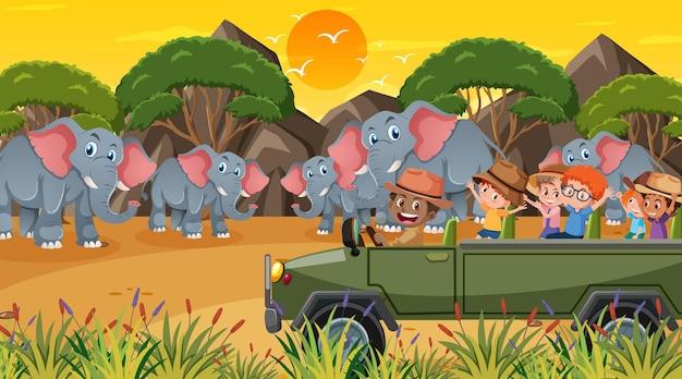 Safari au coucher du soleil avec de nombreux enfants regardant un groupe d'éléphants