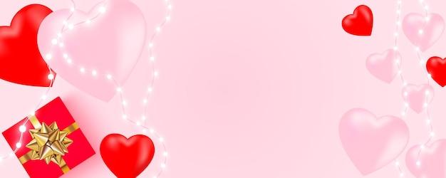 Saint valentin avec guirlande de lumières brillantes, ampoules, coeurs, boîte-cadeau sur rose.