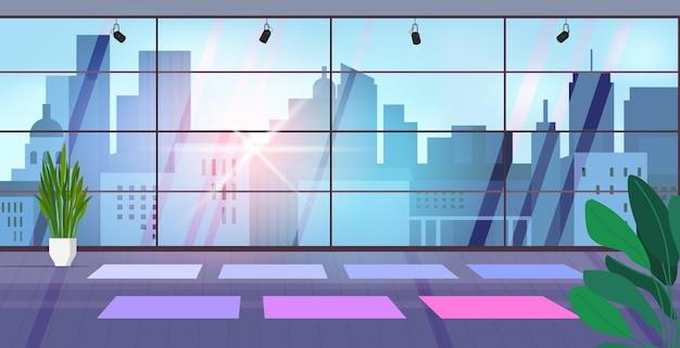 Salle de gym vide pour les entraînements de fitness avec tapis de yoga salle de fitness avec fenêtres panoramiques horizontales