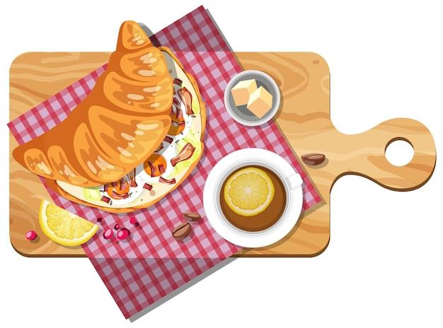Sandwich croissant au petit déjeuner avec une tasse de thé au citron sur une plaque en bois isolée