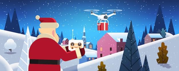 Santa hold contrôleur drone service de livraison pendant la nuit hiver village