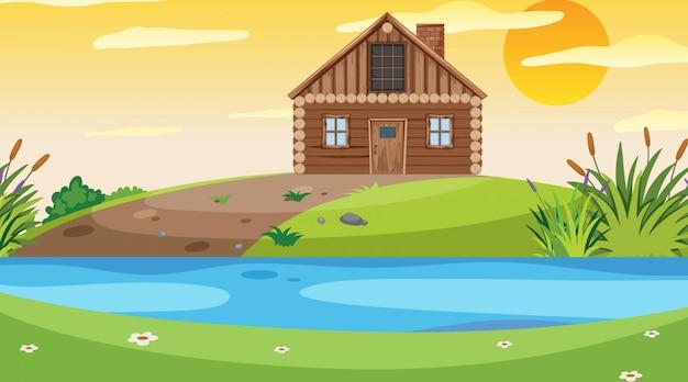 Scène avec chalet en bois sur le terrain au bord de la rivière