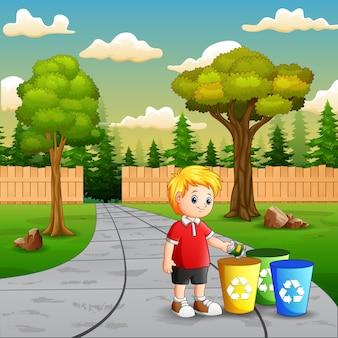 Scène avec un garçon mettant de l'aluminium dans un bac de recyclage