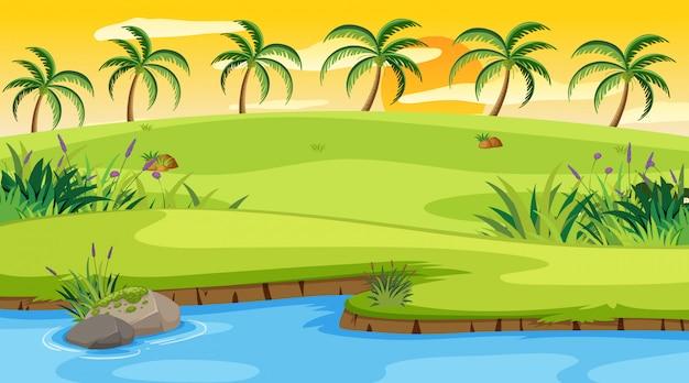 Scène de la nature avec rivière et champ au coucher du soleil