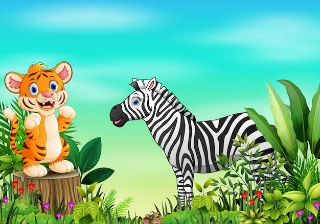 Scène de la nature avec un tigre debout sur une souche d'arbre et un zèbre