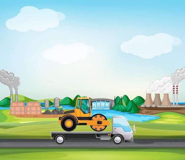 Scène avec rouleau compresseur sur camion en zone industrielle