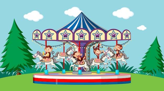 Scène avec des singes mignons à cheval sur le carrousel dans le parc
