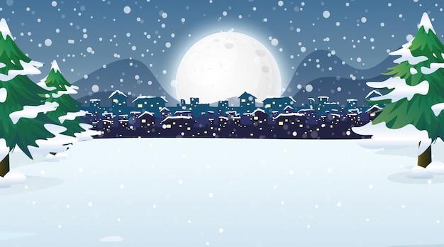 Scène avec la ville dans la nuit enneigée