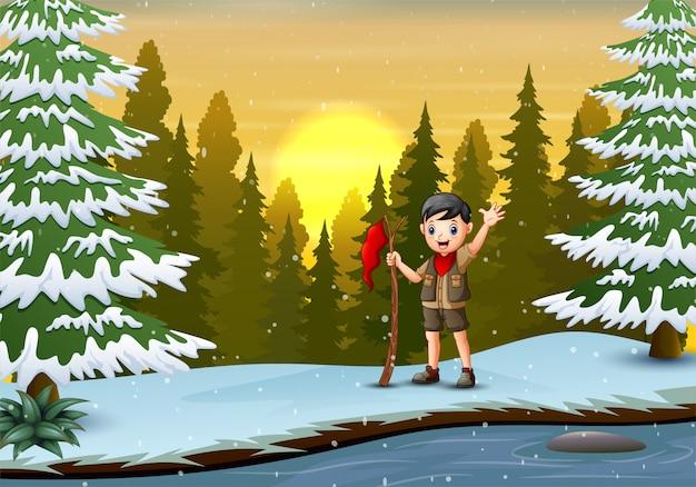 Un scout garçon avec drapeau rouge dans le paysage d'hiver