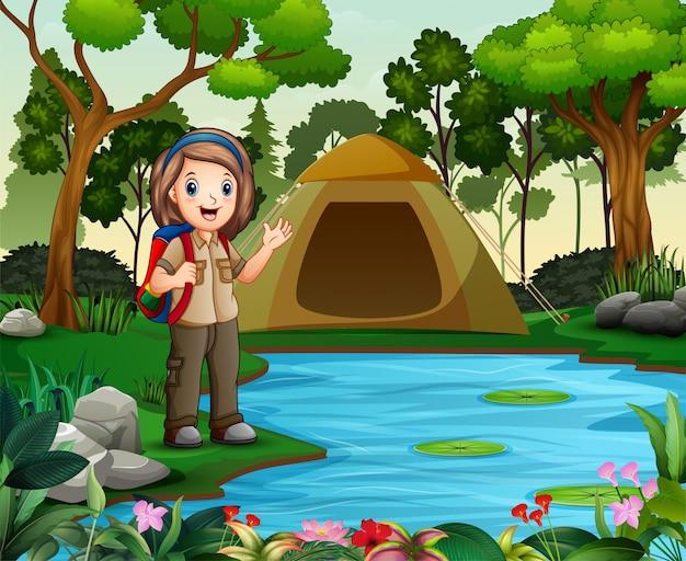 Scout girl on outdoor avec tente et sac à dos