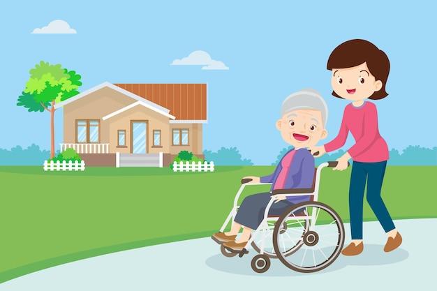 Se promener avec une femme âgée en fauteuil roulant dans le parc