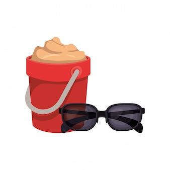 Seau de sable avec des lunettes de soleil sur blanc