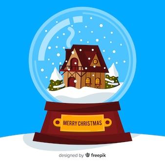 Secouant le globe avec la neige et la maison