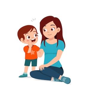 Secret de chuchotement de jeune femme avec le petit garçon mignon
