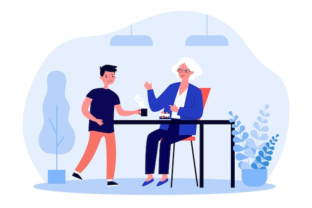 Senior woman sitting at table et petit-fils lui donnant du thé