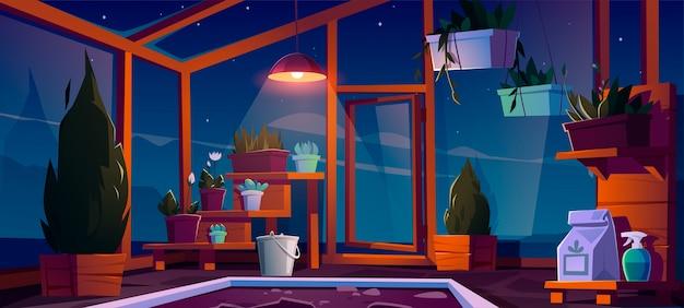 Serre en verre avec plantes, arbres et fleurs la nuit.