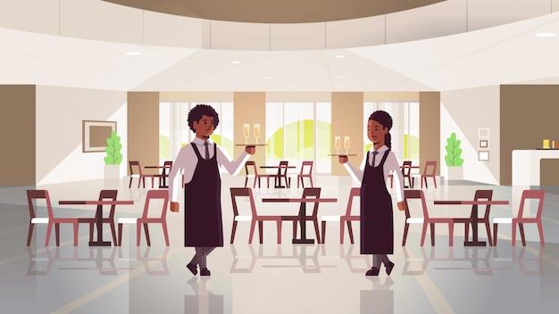 Serveurs, couple, tenue, servir, plateau, deux, coupes, champagne