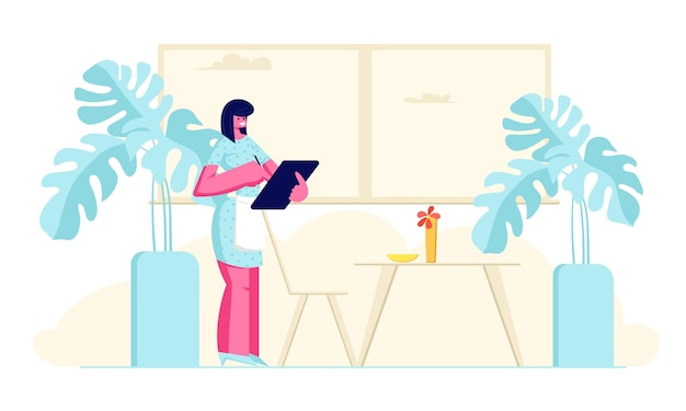 Serveuse dans l'ordre d'écriture de tablier dans un ordinateur portable debout à table dans un café-bar confortable