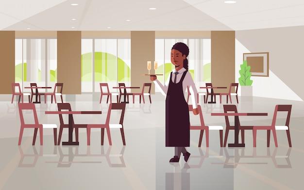Serveuse professionnelle tenant un plateau de service avec deux verres de champagne