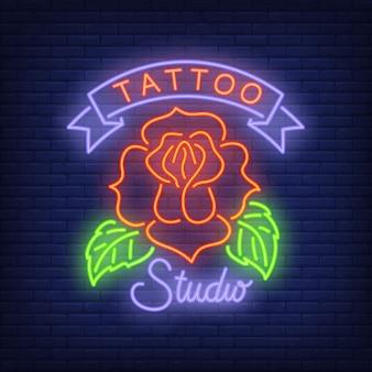 Signe au néon studio de tatouage avec rose. Publicité lumineuse de nuit, enseigne colorée