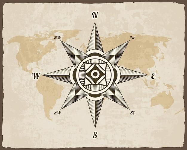 Signe de boussole antique nautique sur la vieille carte du monde de texture papier avec cadre de bordure déchirée.