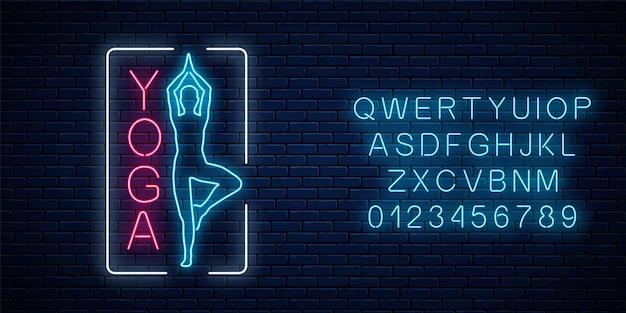 Signe lumineux au néon d'exercices de yoga dans un cadre rectangulaire avec alphabet. panneau publicitaire de rue du club de gymnastique.