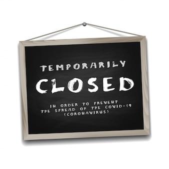 Signe temporairement fermé des nouvelles du coronavirus sur tableau noir dans un cadre en bois.