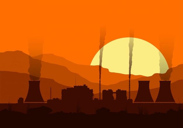 Silhouette d'une centrale nucléaire avec des lumières au coucher du soleil dans les montagnes.