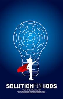 Silhouette d'enfant en costume de super-héros et ampoule avec jeu de labyrinthe. concept d'entreprise pour la résolution de problèmes et la recherche d'idées.