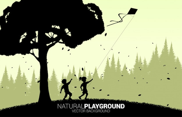 Silhouette de garçon et fille courir avec cerf-volant volant dans le ciel