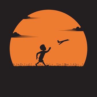 Silhouette un garçon qui court avec un avion en papier au coucher du soleil. rêve, actif, succès