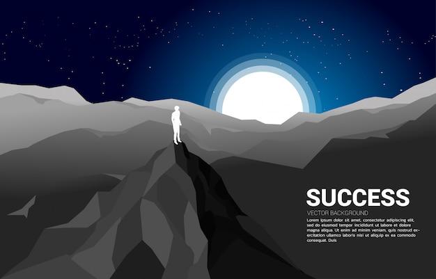 Silhouette d'un homme d'affaires au sommet de la montagne.concept de réussite dans la carrière et la mission