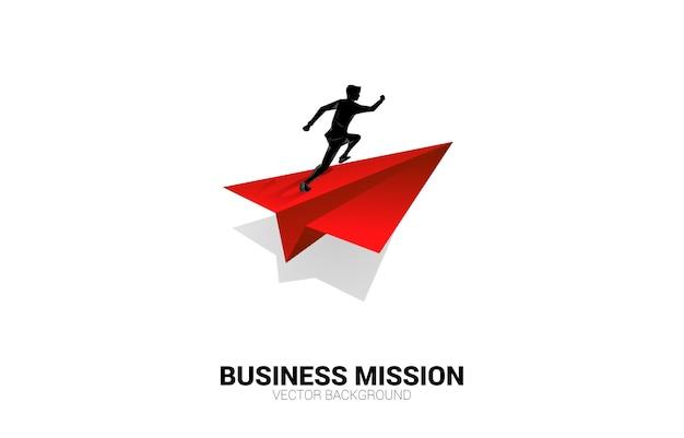 Silhouette d'homme d'affaires en cours d'exécution sur avion en papier origami rouge. concept d'entreprise de leadership, démarrer une entreprise et entrepreneur
