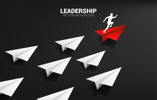 Silhouette d'homme d'affaires en cours d'exécution sur un avion en papier origami rouge, premier groupe de blanc. concept d'entreprise de mission de leadership et de vision.