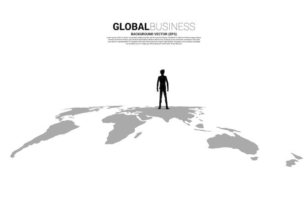 Silhouette d'homme d'affaires debout sur la carte du monde.