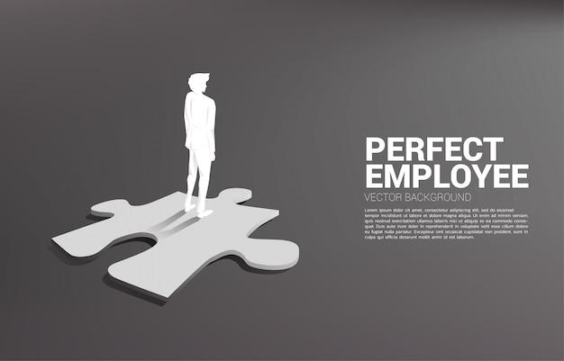 Silhouette d'homme d'affaires, debout sur le morceau de puzzle.