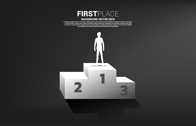 Silhouette d'homme d'affaires debout sur le podium de la première place.