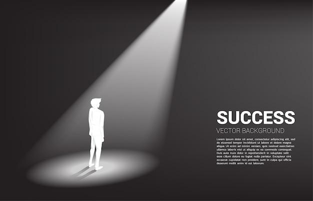 Silhouette d'homme d'affaires debout sous les projecteurs