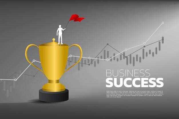 Silhouette d'homme d'affaires avec drapeau rouge sur le trophée du champion