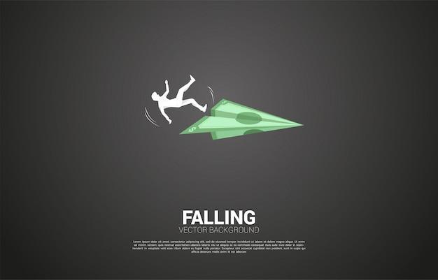 Silhouette d'homme d'affaires glisser et tomber de l'avion en papier origami billets en argent. concept d'échec et d'affaires accidentelles