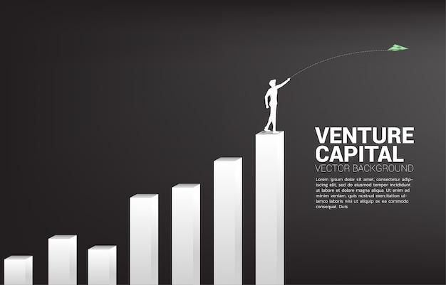 Silhouette d'homme d'affaires jeter l'argent avion en papier origami billet de graphe de pile. concept d'entreprise de démarrage d'entreprise et entrepreneur