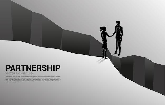 Silhouette d'homme d'affaires poignée de main de l'autre côté de la vallée. concept de partenariat de travail d'équipe et accord de réussite.