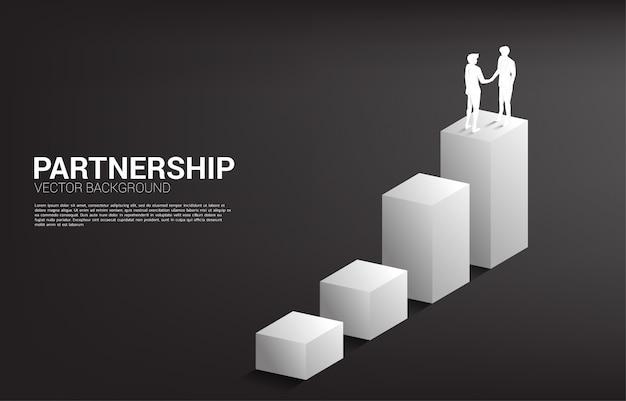 Silhouette d'homme d'affaires poignée de main sur le graphique de plus en plus. concept de partenariat et de coopération de travail d'équipe.