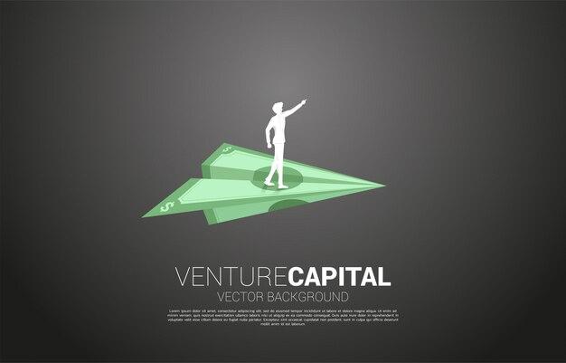 Silhouette d'homme d'affaires pointe en avant sur l'avion en papier origami billets en argent. concept d'entreprise de démarrage d'entreprise et entrepreneur