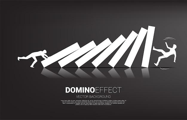 Silhouette d'homme d'affaires poussant pour effondrer le domino à un autre homme d'affaires. concept d'entreprise de perturbation des affaires et effet domino