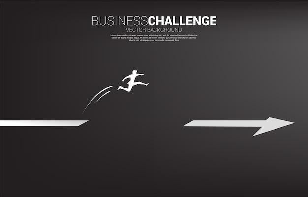 Silhouette d'homme d'affaires sautant à travers l'écart sur la flèche. concept de personnes prêtes à démarrer une carrière et une entreprise