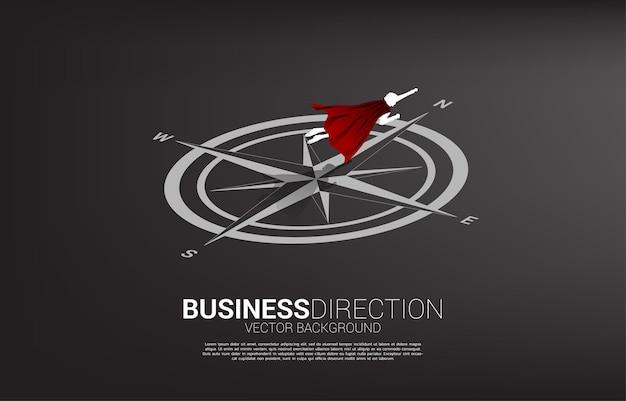 Silhouette d'homme d'affaires survolant la boussole sur le sol. concept de cheminement de carrière et de direction commerciale